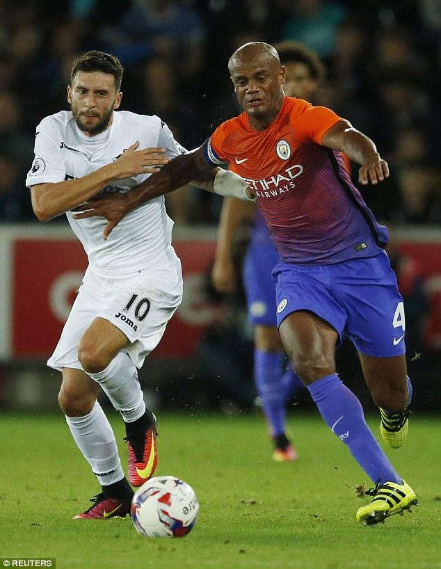 Swansea City's Borja Baston (left) battles with Manchester City's Vincent Kompany in midweek