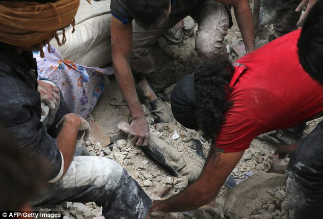 Missiles rained down on rebel-held areas of Syria's Aleppo on Friday, causing widespread destruction that overwhelmed rescue teams, pictured is a child being pulled from rubble