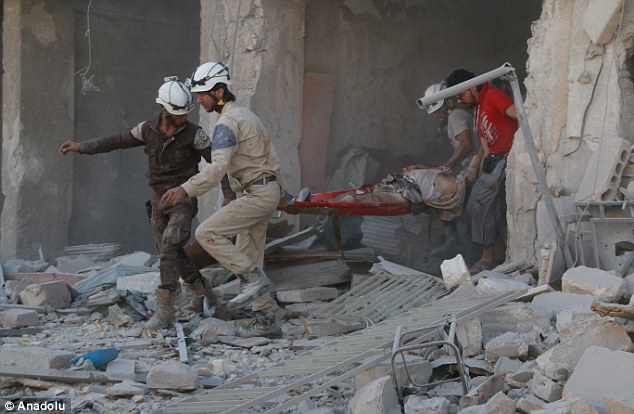 Rescue teams are pictured carrying a casualty of a stretcher after the Syrian regime forces airstrikes hit Aleppo's opposition controlled Al-Ansari town
