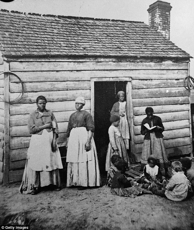 A group of women and children, presumably slaves, sit and stand around the doorway of a rough wooden cabin in the Southern United States during the mid 19th Century
