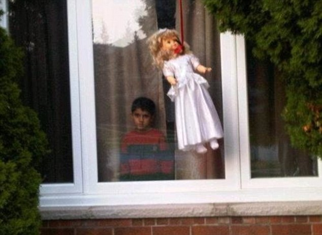 One alarming image shows a young boy standing at a window staring unblinkingly out while a doll with a noose around her neck hangs outside