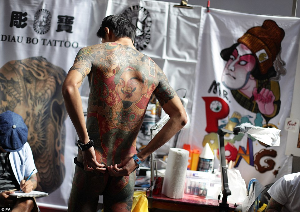 Graffiti artist Debe, aged 28 and from Taiwan, has a jolly-looking bearded figure tattood on his very colourful back
