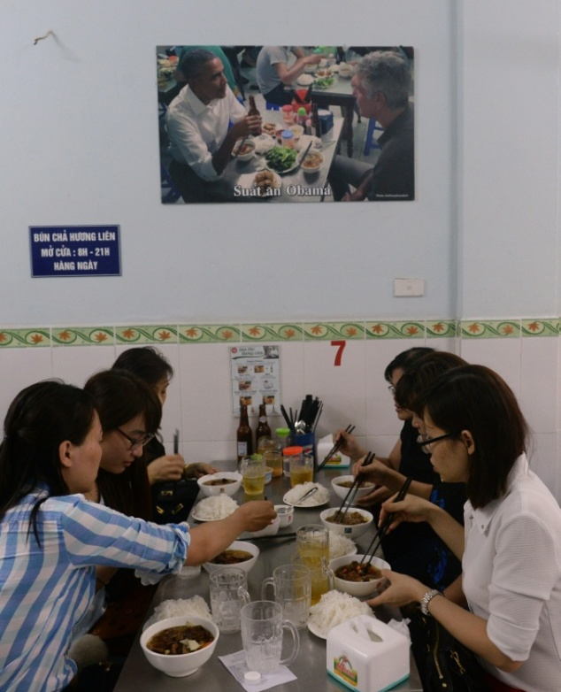 Customers eating under a picture showing US President Barack Obama eating during his visit to the Bun Cha Huong Lien restaurant last May in Hanoi
