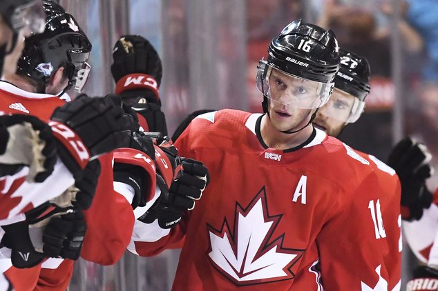 Team Canada's Jonathan Toews celebrates his second goal of the game against Team Europe with teammates on the bench during the second period of a World Cup o...