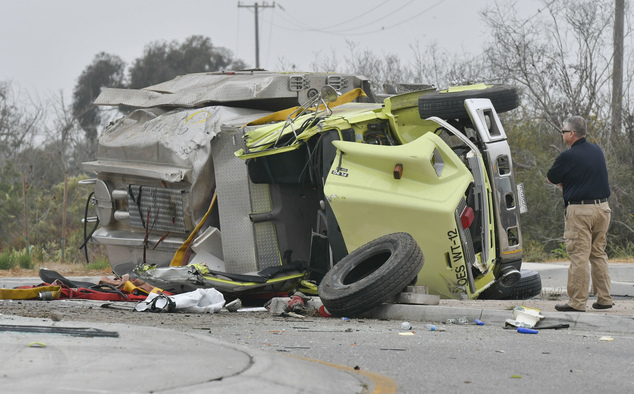 A California Highway Patrol investigator looks at the wreck of a water tender fire truck involved in a rollover crash near Vandenberg Air Force base that too...