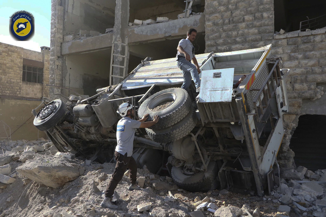 In this photo provided by the Syrian Civil Defense group known as the White Helmets, rescue workers remove a destroyed ambulance outside the Syrian Civil Def...