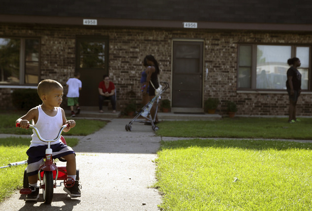 FILE - In this Aug. 3, 2016 file photo, Joseph Russell, 2, rides his tricycle outside his home at the West Calumet Housing Complex in East Chicago, Ind. The ...