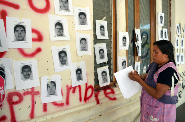 Genoveva Sanchez, mother of Israel Caballero Sanchez, one of the 43 missing students, pastes images of the missing students on the walls of the main Guerrero...