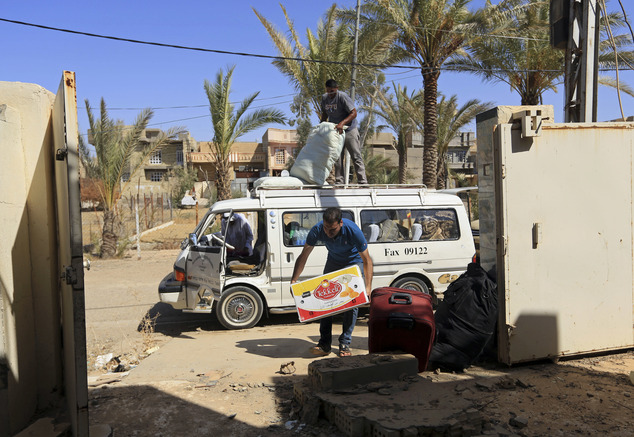 FILE -- In this Wednesday, Sept. 21, 2016 file photo, internally displaced Iraqis unload their belongings after returning to Fallujah, 40 miles (65 kilometer...