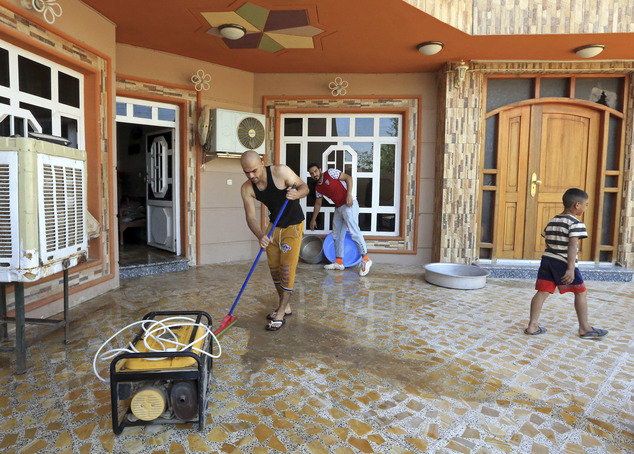 FILE -- In this Wednesday, Sept. 21, 2016 file photo, returning internally displaced Iraqis clean their house after returning to Fallujah, 40 miles (65 kilom...