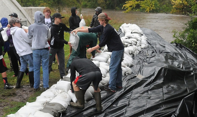 Residents and volunteers in St. Clair, Minn., lay down sandbags to protect the citys' water treatment plant from the rising Le Sueur River Thursday morning, ...