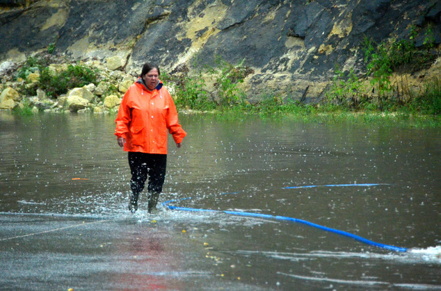 A woman who was helping with the sand-bagging operation at the Faribault Cheese Cave, in Faribault, Minn., walks through the water on Thursday, Sept. 22, 201...