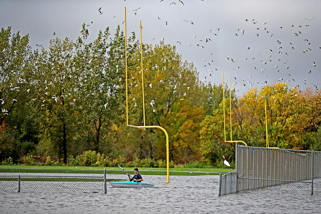 Justin Sampson, a member of the Waseca High School football team checks out the flooding on the football field from a kayak near the Waseca High School, Thur...