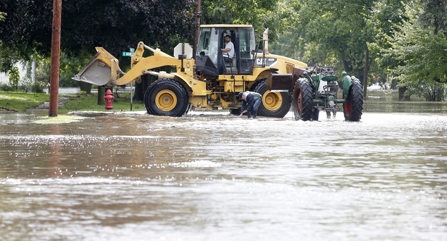 Men move a tractor to higher ground in Greene, Iowa, as the Shell Rock River rises into residential areas Thursday, Sept. 22, 2016. Several Midwestern states...