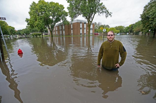 Ellery Forsythe makes his way around his neighborhood assessing the flooding on a Waseca street, Thursday, Sept. 22, 2016, in Waseca, Minn. Heavy rain has fl...