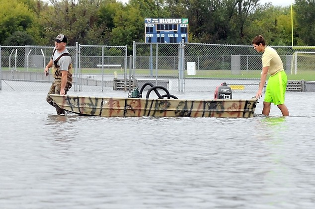Two men use a boat to transport a pump and generator across the Waseca High School's parking lot to the flooded Community Ice Arena Thursday, Sept. 22, 2016 ...