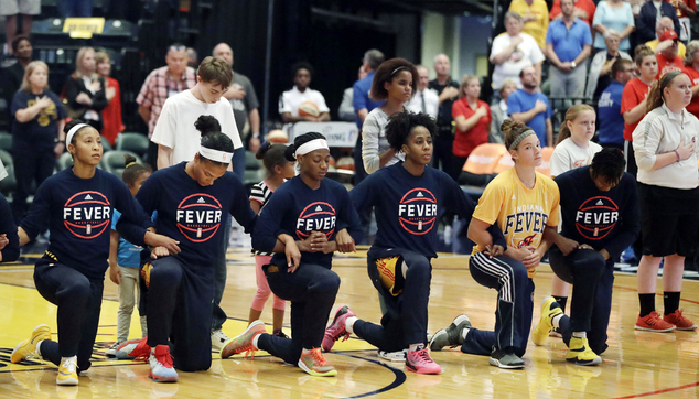 Members of the Indiana Fever kneel during the playing of the national anthem before the start of of a first round WNBA playoff basketball game, against the P...
