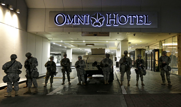 Members of the North Carolina National Guard stand guard outside the Omni Hotel as demonstrators take to the streets following Tuesday's police shooting of K...