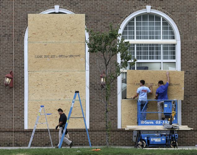 Workers cover large windows with plywood at a downtown hotel after a second night of violence following Tuesday's fatal police shooting of Keith Lamont Scott...