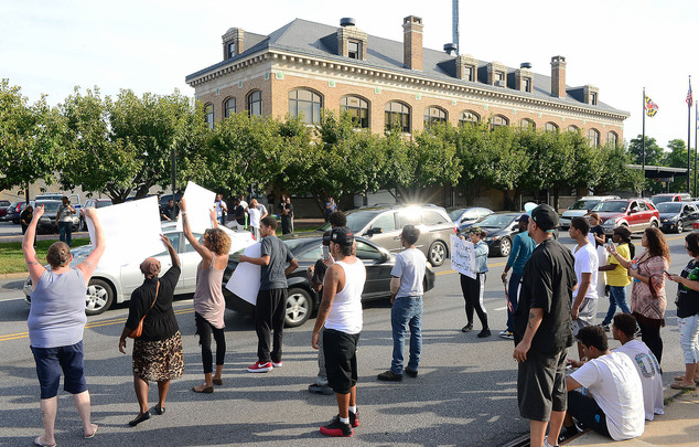 Protesters are pictured while holding up signs outside the police department