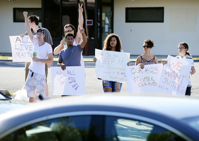 Protesters gather along Burhans Boulevard across from the Hagerstown Police Department station during rush hour on Thursday
