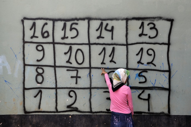 An Afghan girl counts in Greek the numbers on the wall during a lesson by a non governmental organization at a refugee camp in the western Athens' suburb of ...