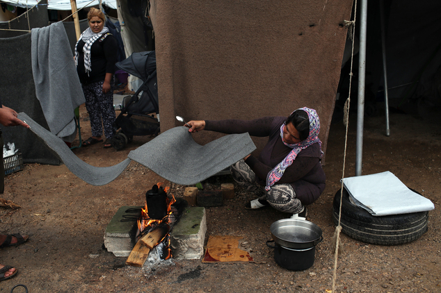 A Syrian woman covers her makeshift fire with a plastic sheet during rainfall at Ritsona refugee camp north of Athens, which hosts about 600 refugees and mig...