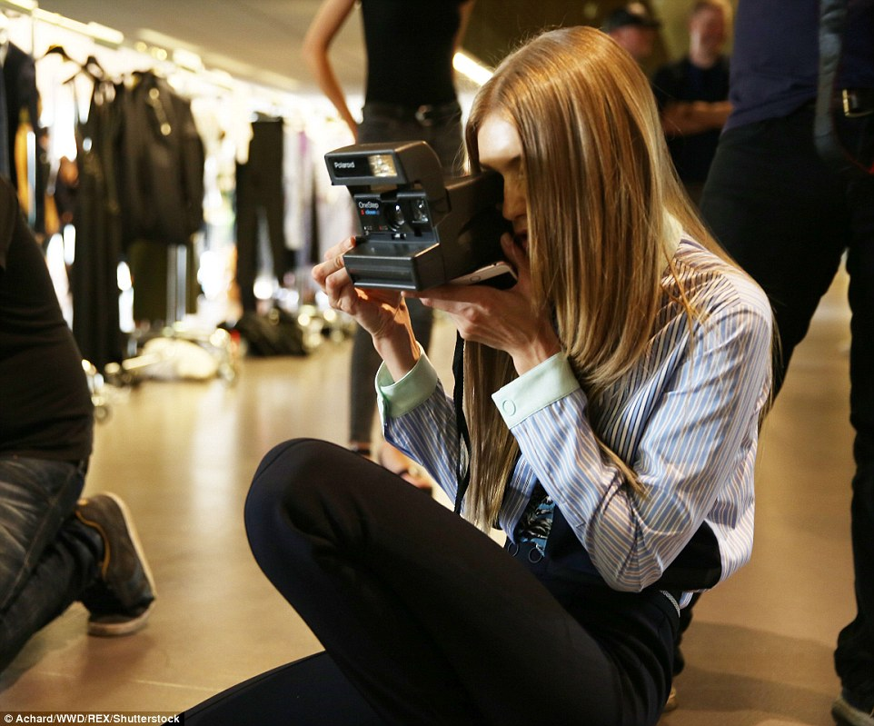 Snap happy: Gigi turned the tables as she became a photographer for the night capturing the backstage shots