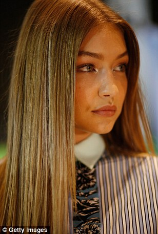 Backstage beauty: Gigi was a vision of beauty as she prepared for the show backstage with clips smoothing her golden locks