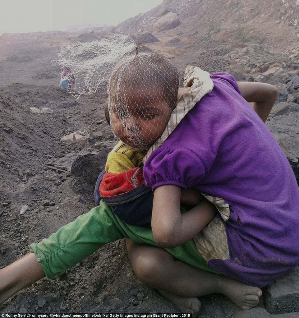Children wait for their parents to return from work at a coal mine in Jharia in India's Jharkhand state