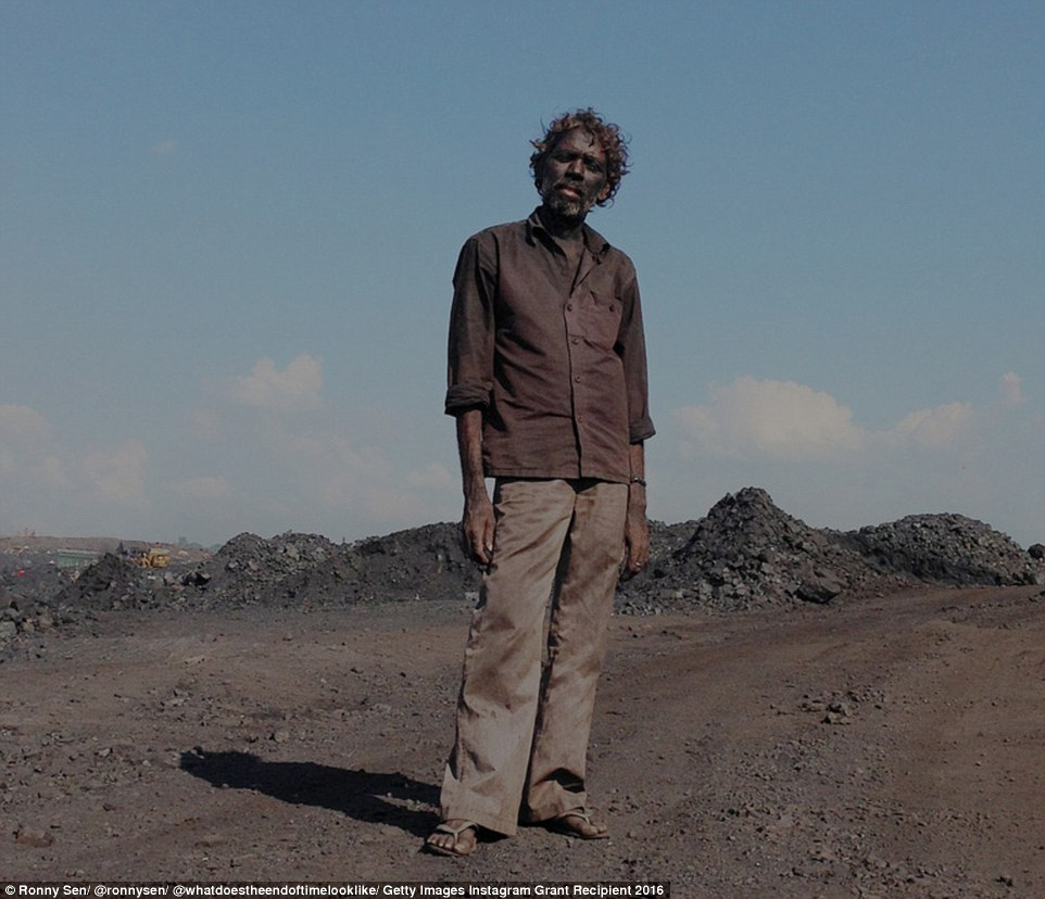 A labourer stands outside one of the coal mines in Jharia, India. He will make $2 (£1.54) for loading five lorries with coal. It is back-breaking work in stifling temperatures