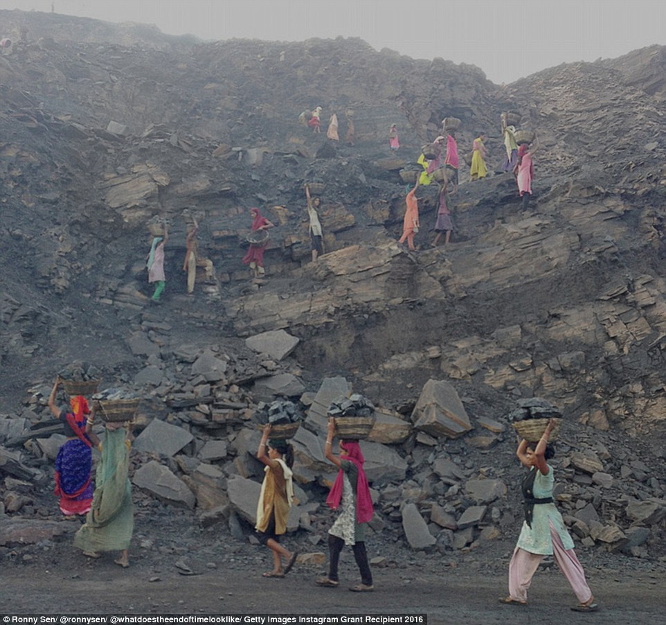 Coal thieves - in this case women whose brightly coloured clothes clash with the greyness of the open-cast mine - work very early in the morning before the mine officials arrive in Jharia