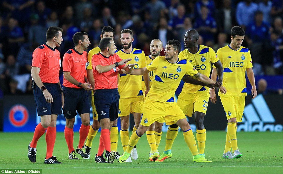 Porto players argue with Turkish referee Cuneyt Cakir as the leave the pitch at half-time