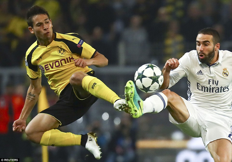 Dortmund left back Raphael Guerreiro (left) goes airborne to contest a loose ball with Real defender Dani Carvajal