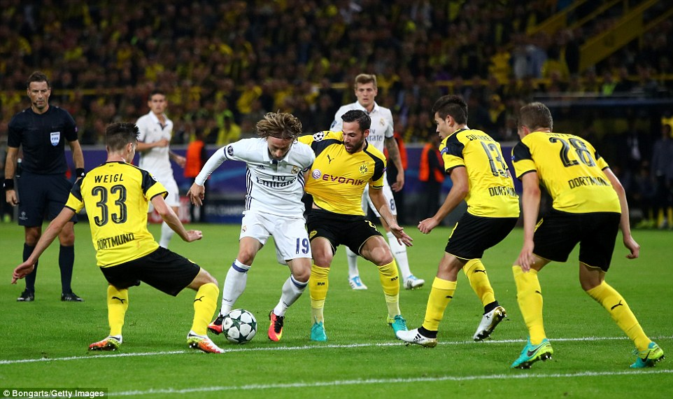 Real midfielder Luka Modric looks to weave his way through a throng of Dortmund defenders