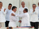 Colombia¿s President Juan Manuel Santos, front left, and the top commander of the Revolutionary Armed Forces of Colombia (FARC) Rodrigo Londono, known by the alias Timochenko, shake hands after signing the peace agreement between Colombia¿s government and the FARC to end over 50 years of conflict in Cartagena, Colombia, Monday, Sept. 26, 2016. Behind, from left, are U.N. Secretary General Ban Ki Moon, Mexico's President Enrique Pena Nieto, Peru's President Pedro Pablo Kuczynski, Cuba's President Raul Castro, and Spain's former King Juan Carlos. (AP Photo/Fernando Vergara)