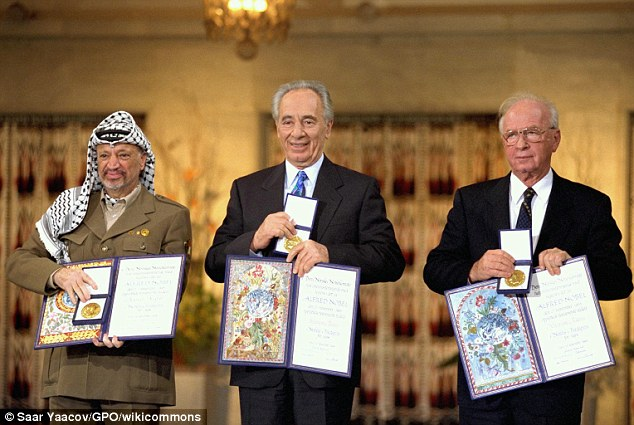 Peres (center), PLO chairman Yasser Arafat (left), and then-prime minister Yitzhak Rabin (right) are awarded the Nobel Prize in Oslo on December 10, 1994