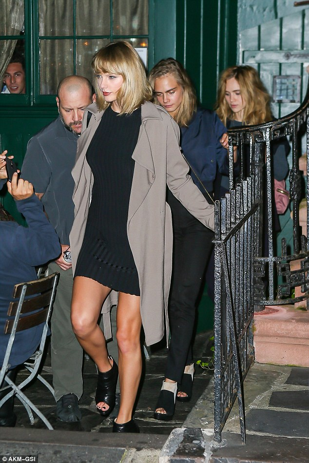 Stylish: Taylor wore a tight knit dress and long trench for their girls' night out
