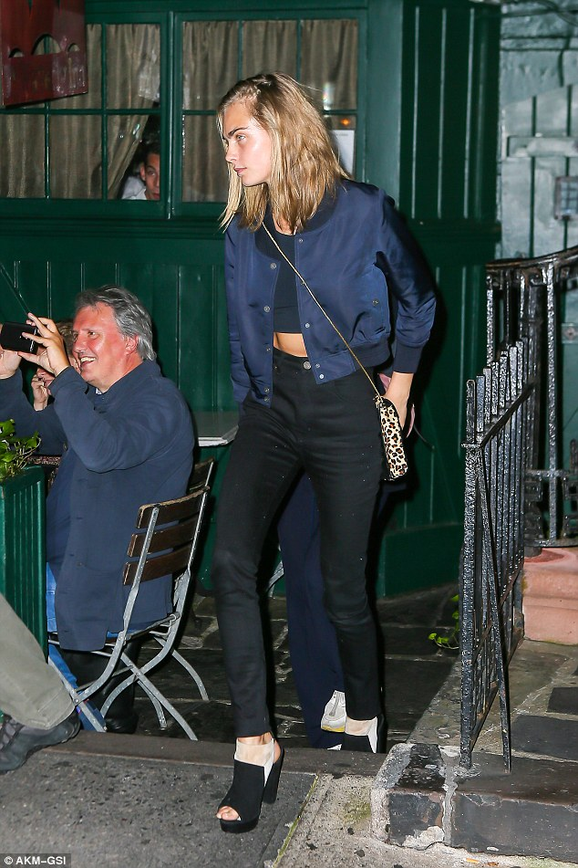 Supermodel style: Cara flashed her midriff in a black crop top and blue bomber jacket