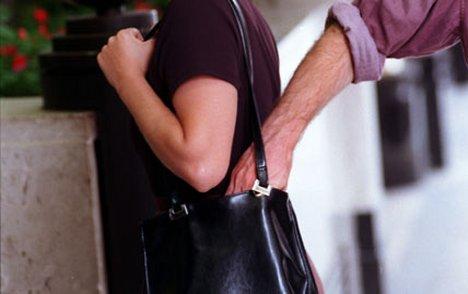 Pickpocket dipping into a handbag